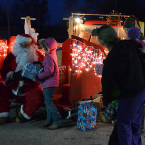 Santa handing out gifts to County Kids